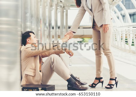 Business woman standing hand to help male businessman,Consultation and assistance,team work. #653150110