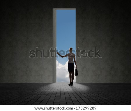 business woman standing near a hole in the wall of the hole at her light falls