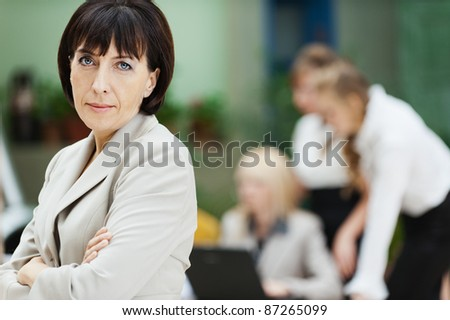 business woman stands behind collective laptop work