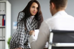 Business woman stands leaning on table in front man. Distinctive features female leader. Increase motivation and self-esteem employees. Personal conversations and encouragement subordinates