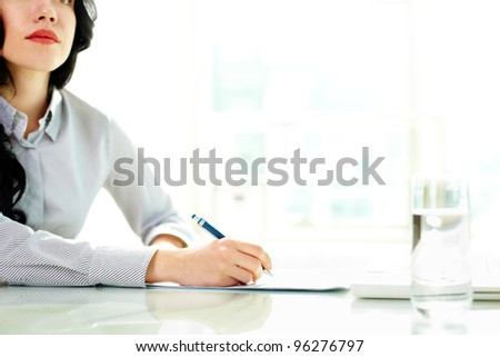 Business woman taking notes at seminar - stock photo