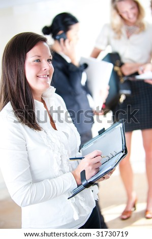Business woman taking notes with colleagues in background - Shutterstock ID 31730719