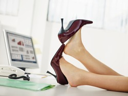 business woman taking off shoes in office.