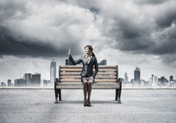 Business woman taking selfie photo or chatting with smartphone. Attractive girl using mobile phone on wooden bench. Mobile marketing and communication. Modern cityline panorama with cloudy storm sky.