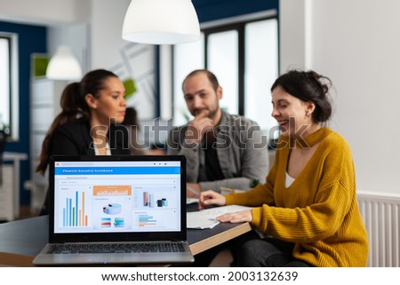Business woman talking about financial project, taking notes, discussing start up ideas using laptop. Diverse employees gathered in co-working, working process in busy company, teamwork help concept Photo stock ©