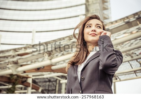 Business woman talking at phone - Asian woman with elegant dress and skyscraper in the background  - Business,technology,multiracial concepts