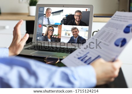 Business woman talking to her colleagues in video conference. Business team working from home using laptop.