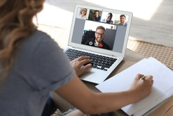 Business woman talking to her colleagues in video conference. Businessteam working from home using laptop.