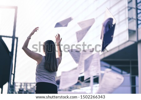 Photo of  Business woman throwing work papers in the air. Stress from workload. Person going home or leaving for vacation. Employee got fired. Job or project done. Difficult workday over. Outside of office.