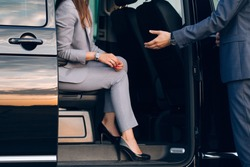Business woman travelling in vip car transfer. Driver helping woman to get outside the car
