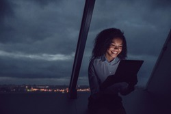 Business woman uses a tablet sitting by the window in the office on a background of a night city.