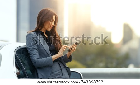 Business Woman Uses Smartphone While Leaning on Her Premium Class Car. Big City with Skyscrapers in the Background.