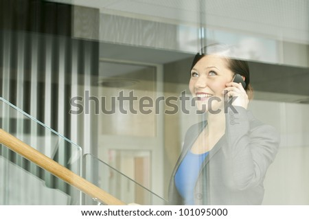 Business woman using a mobile phone at the office