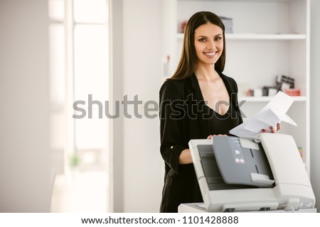 Business woman using a printer. Beautiful business woman printing a document.  Business woman printing a document for a new company project.