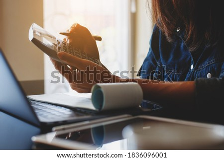 Business woman using calculator and sign cheque, work on laptop computer at office.Payment and payroll concept.