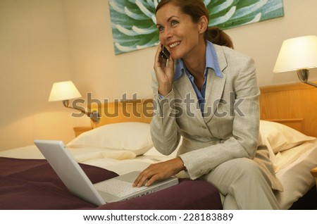 Business woman using laptop and handy in hotel room
