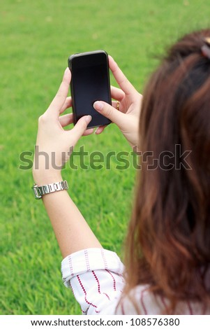 Business woman using mobile smart phone in the park