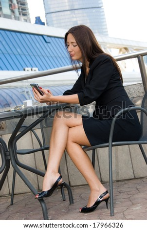 Business woman using palmtop outdoors