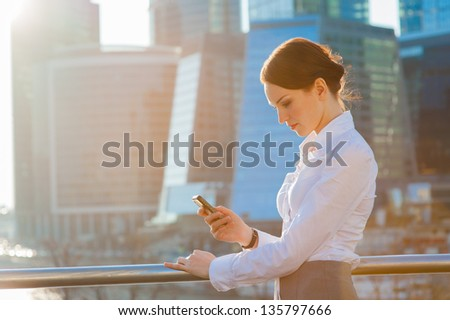 Business woman using smartphone. Sun beams, lens flare stock photo