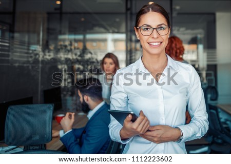Business woman using tablet in front of her colleagues in the office.Business,people,teamwork and office concept. #1112223602