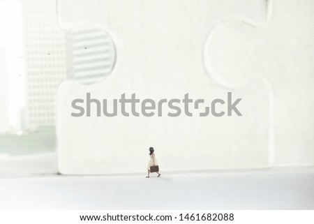 business woman walking in a surreal city of skyscrapers and giant puzzles #1461682088