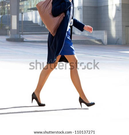 Business woman walking on the background of the office. The modern woman.