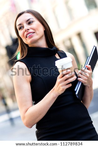 Business woman walking outdoors holding a cup of coffee