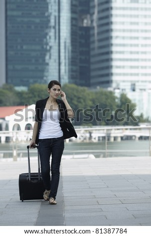 Business woman Walking with a wheeled Suitcase on phone
