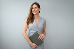 Business woman wearing grey dress, holding books, looking away and standing near to copy space. Isolated female portrait.