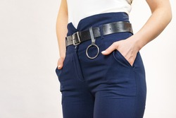 Business woman wearing suit, blue high waist pants with black leather trouser belt. Clothing detail.