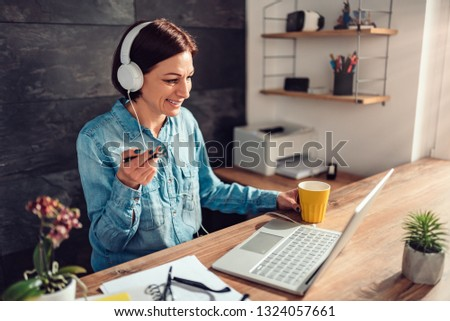 Business woman wearing white headphones doing video call at work