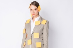 Business woman wears light brown suit standing on white background with a lot of post it on her body
