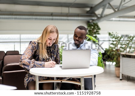 Business woman with African man working on a laptop in the office Foto stock ©