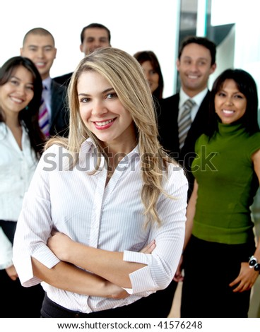 Business woman with arms crossed and her team behind at the office