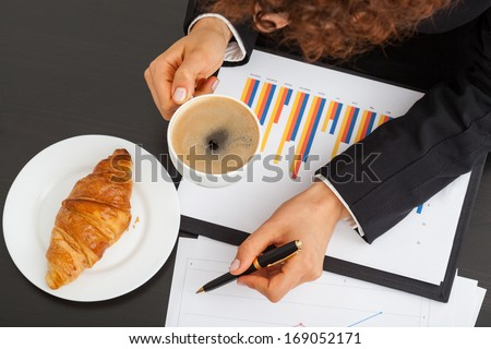 Business woman with bar chart, coffee and snack - stock photo