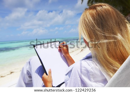 business woman with blank paper lying on a chaise lounge in the tropical ocean coast