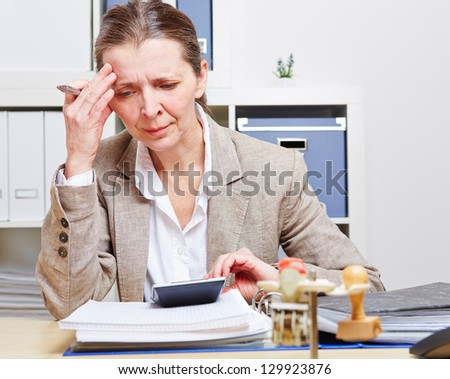 Business woman with burnout sitting in her office at the desk over files