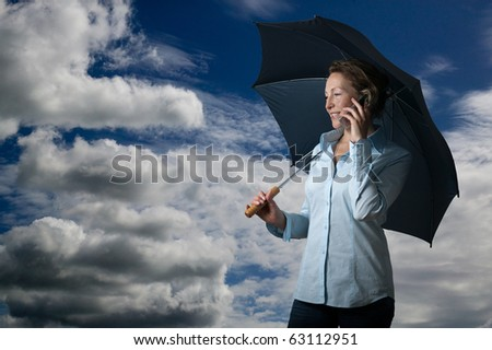 business woman with cell phone and umbrella