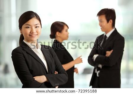 Business woman with colleagues at the back out of focus