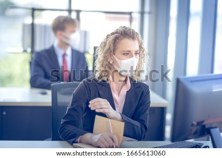 Business woman with curly blonde hair wearing a mask sitting in office, Concept,contagious disease, coronavirus.covid2019