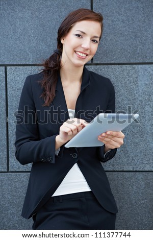 Business woman with digital tablet computer leaning on wall