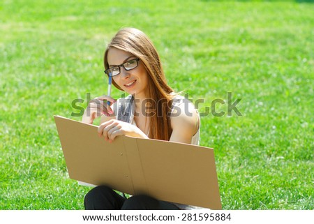 Business woman with folder, paper notebook and pen sitting in the park on conference and read article