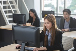 Business woman with headset as the callcenter or business telesales working on desk with colleagues