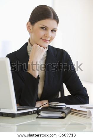 Business woman with laptop looking at camera