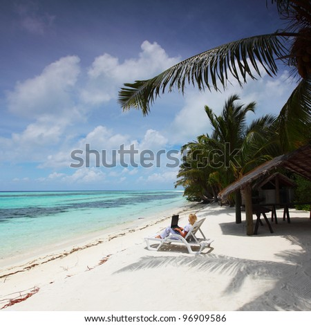 business woman with laptop lying on a chaise lounge in the tropical ocean coast - stock photo