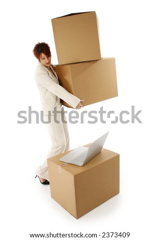 Business woman with large boxes looking at laptop.