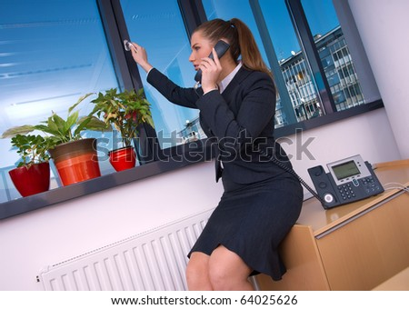 business woman with phone opening office window