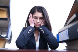 Business woman with pile of folders and binders looking overwhelmed with work after a long day