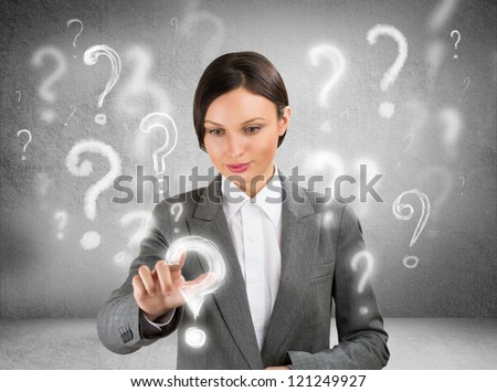Business woman with question symbols around her. Choosing one and pressing on it