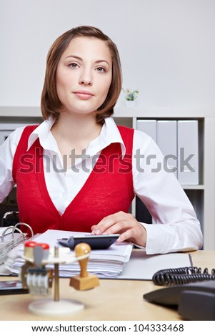 Business woman with serious look sitting at her desk in the office working